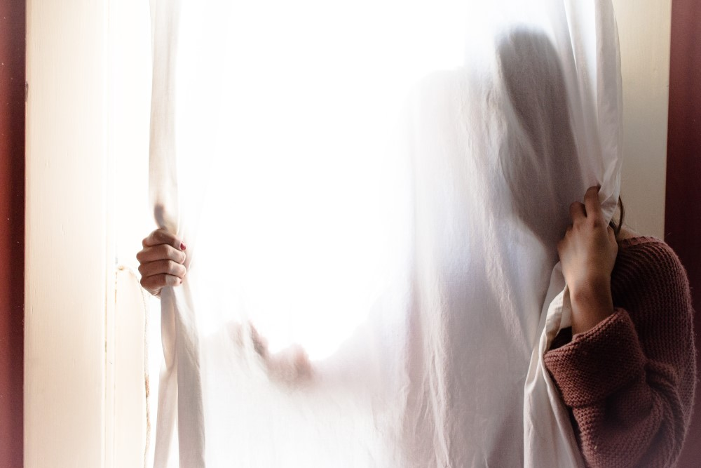 Woman hiding behind a curtain