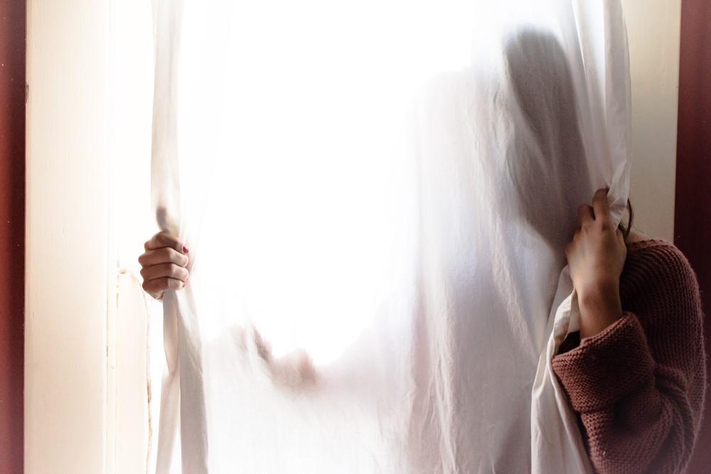 Woman hiding behind a curtain