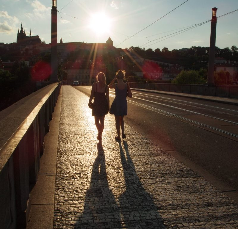 Two women walk on a bridge, in Europe, into the sun