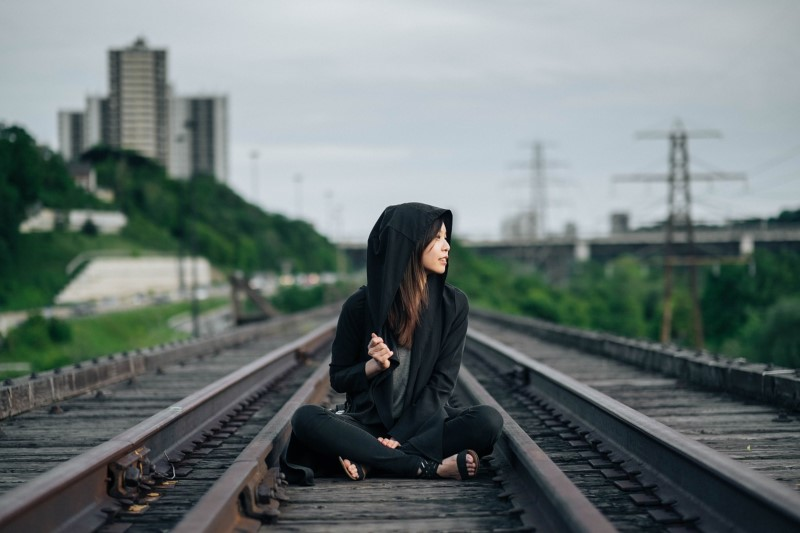 Woman sitting on railroad tracks