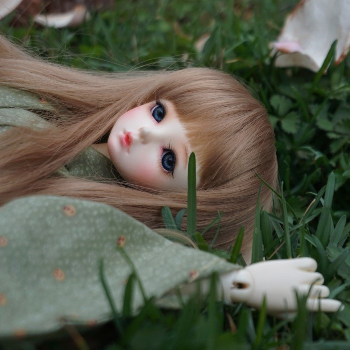 doll with make-up lying on grass