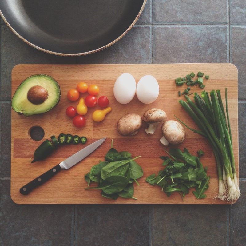 veggies and eggs on cutting board with knife and pan