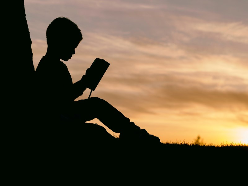 silhouette of boy reading a book outside