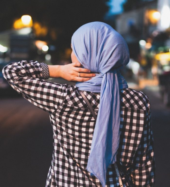woman with headscarf touching her neck