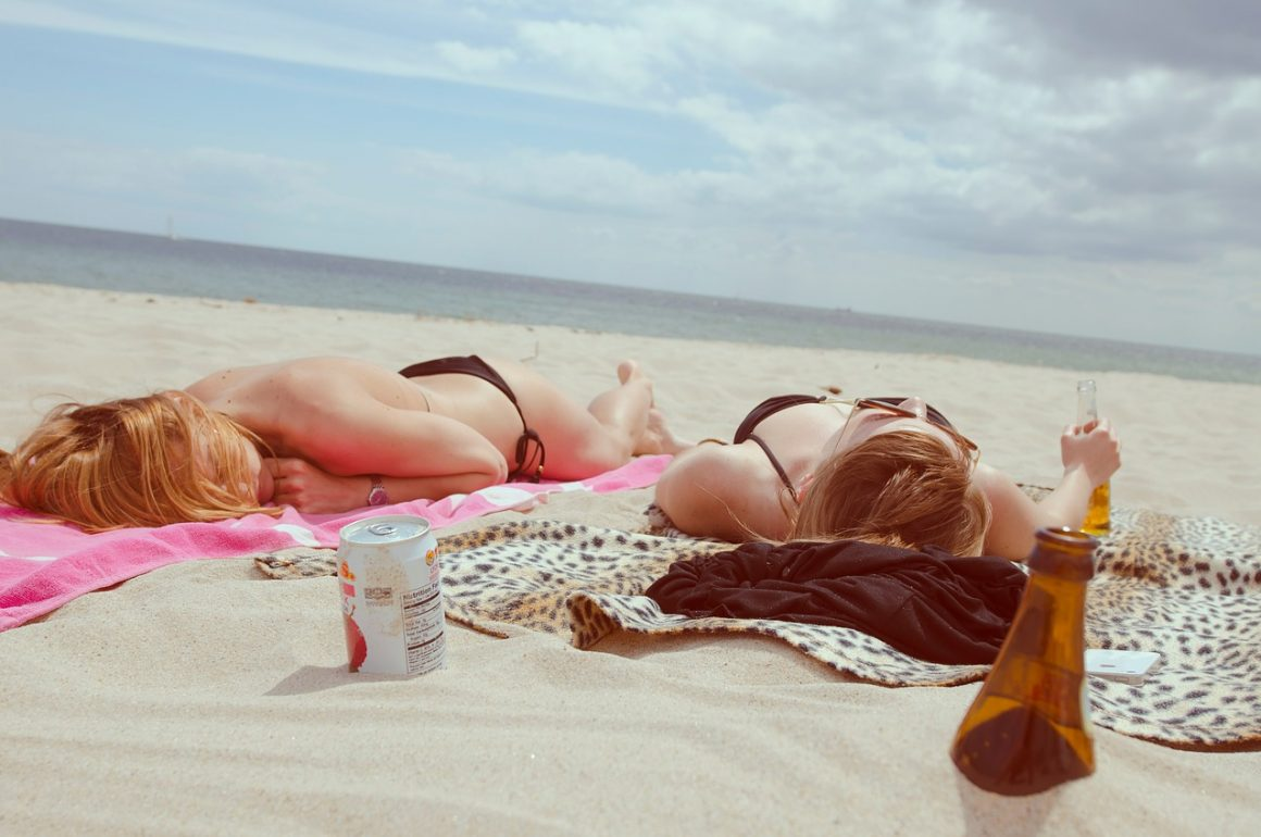 two women lying on beach, sunning, drinking