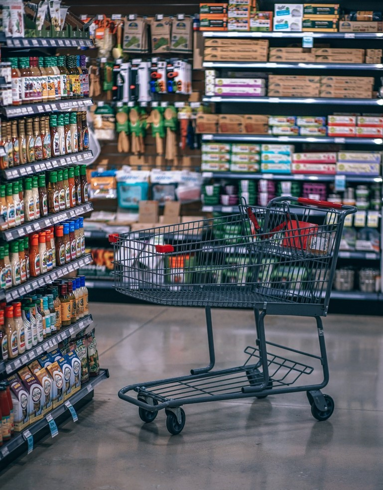 empty shopping cart in full grocery store aisle