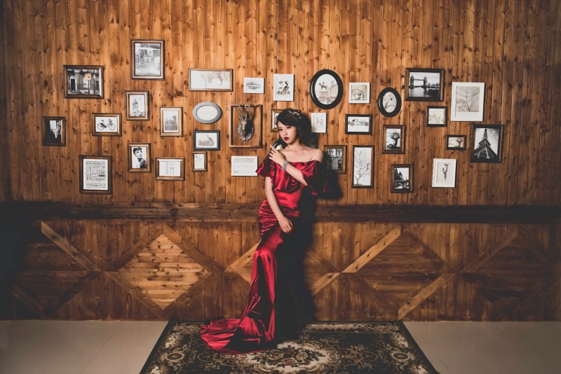 woman in red dress in front of framed photographs hanging on wood paneled wall