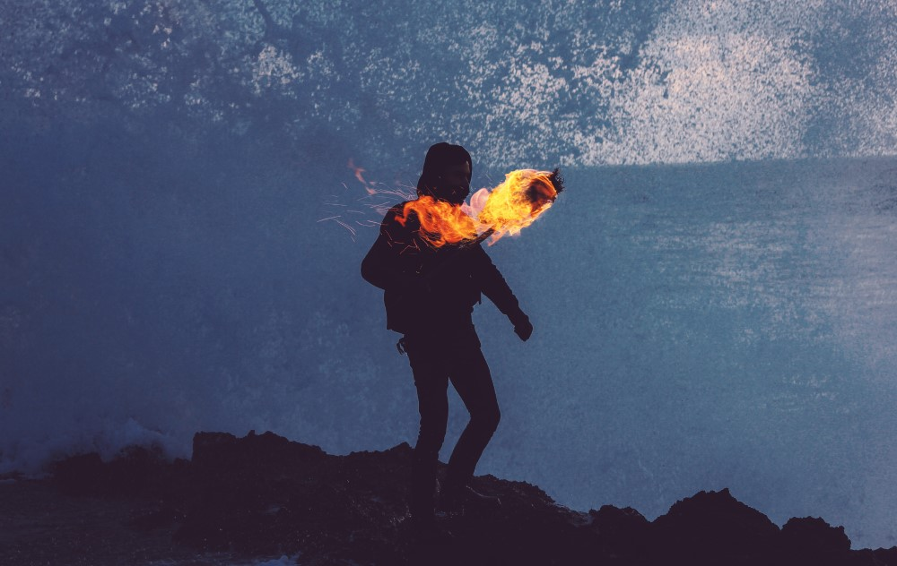 person on a rock at night in control of a torch
