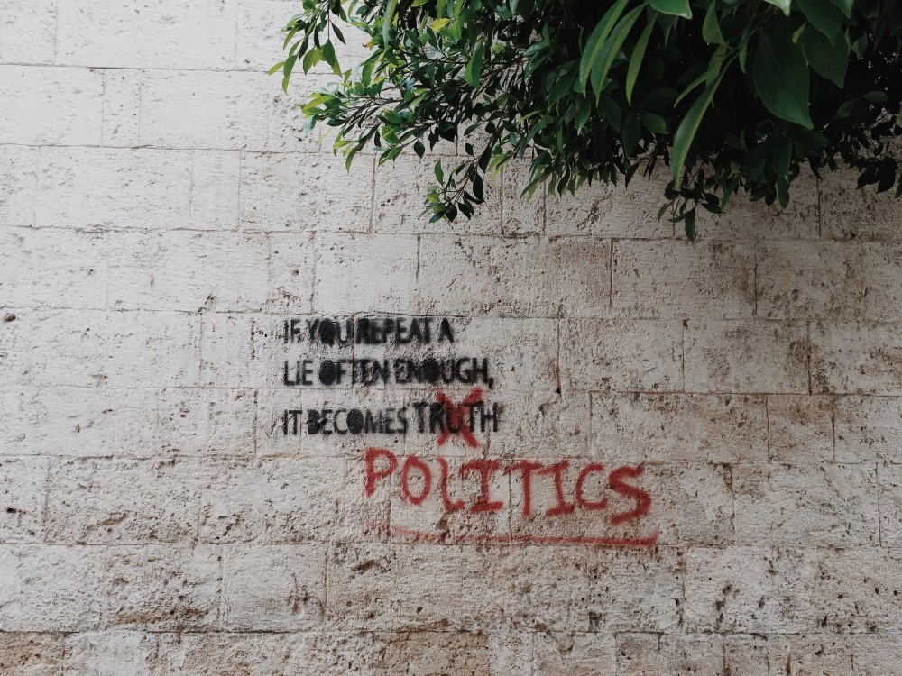 Graffiti on a wall that says If you repeat a lie often enough, it becomes politics