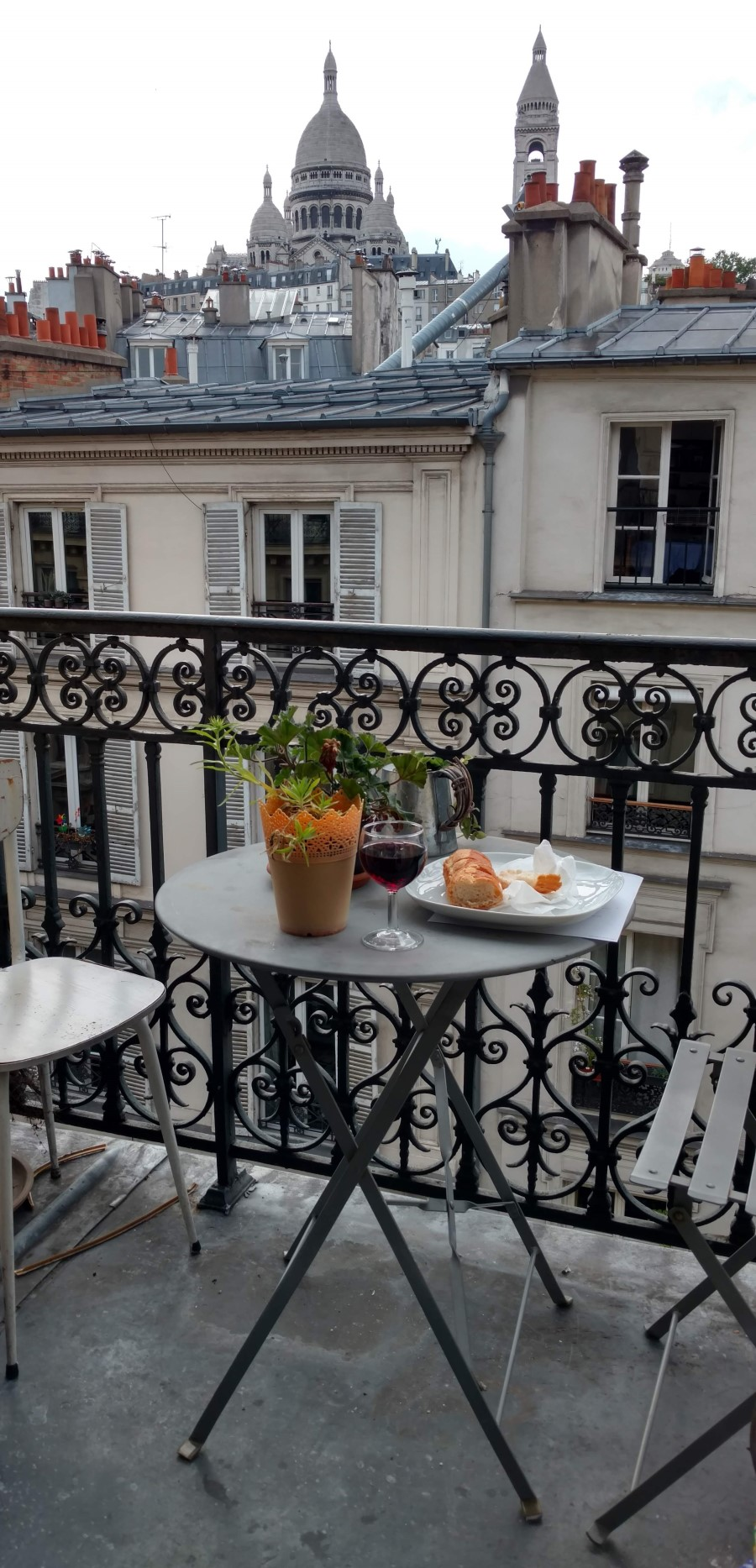 The balcony of my Airbnb home in Montmartre, Paris. A glass of wine and French bread on a table with two chairs, with a view of Sacré-Cœur.
