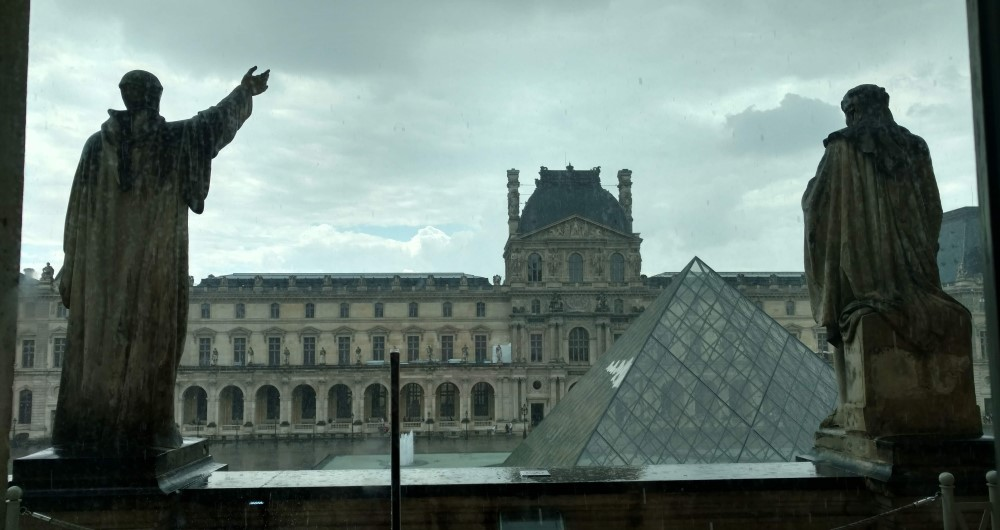 Looking outside at the Louvre at the pyramid and two statues