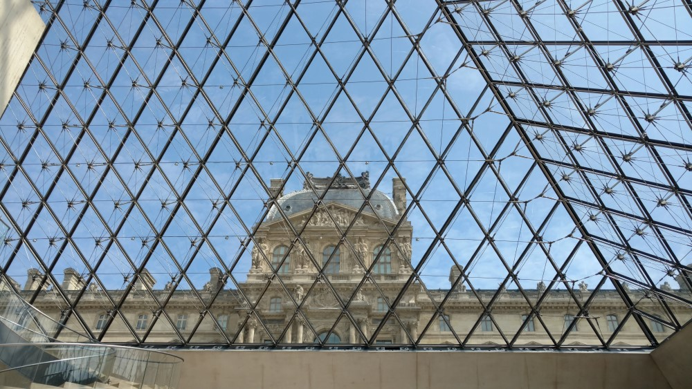 Inside the foyer of the Louvre, looking up and out through the right-side-up pyramid