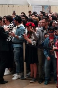Young woman in traditional Parisian attire, in the crowd before the Mona Lisa at the Louvre