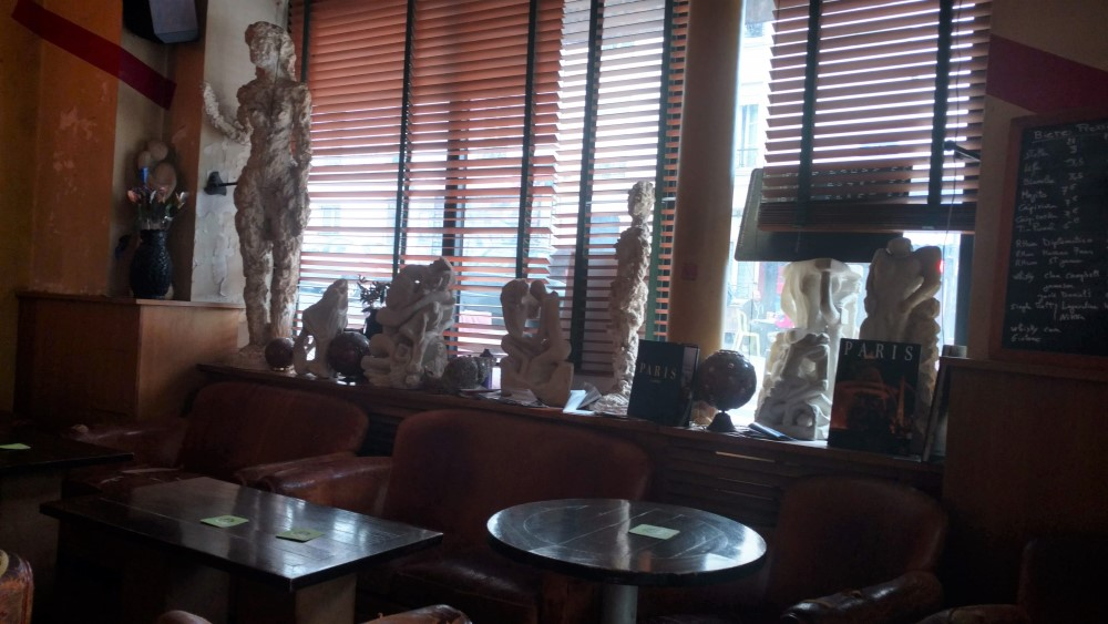 Scultpture and statues in a cafe window in Paris