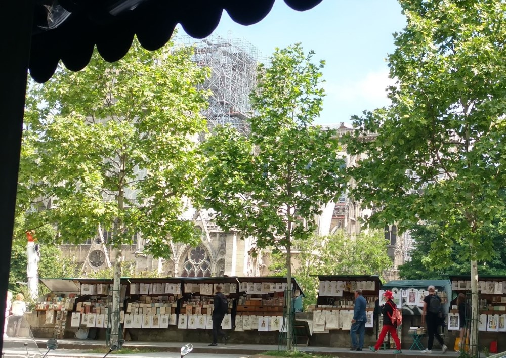 Looking out from a cafe in Paris at street art vendors and Notre Dame