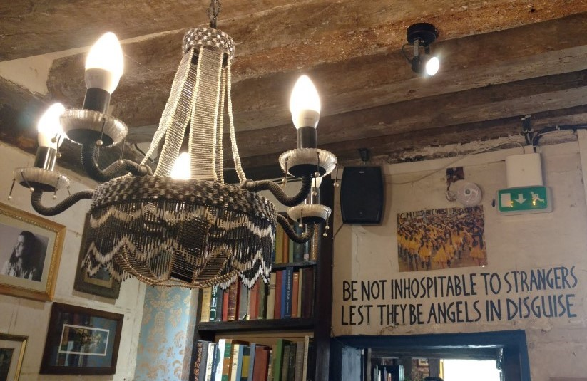 Interior of Shakespeare and Company, a bookstore in Paris. Sign on the wall says BE NOT INHOSPITABLE TO STRANGERS LEST THEY BE ANGELS IN DISGUISE