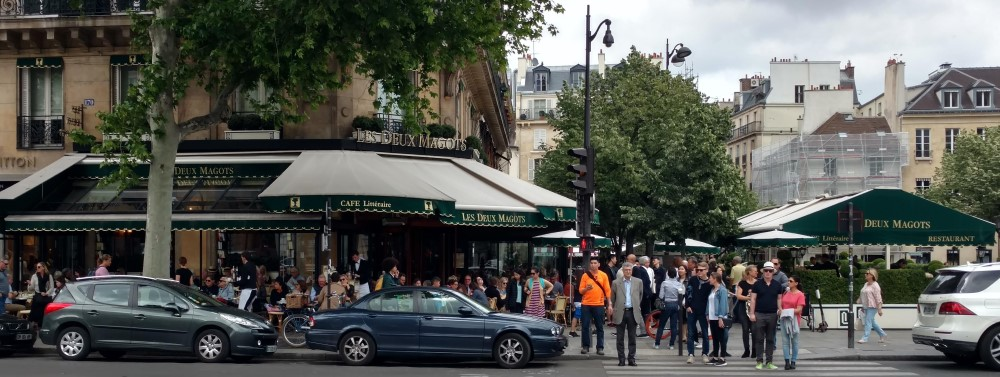 Les Deux Magots cafe in Paris with people wearing different styles of clothing