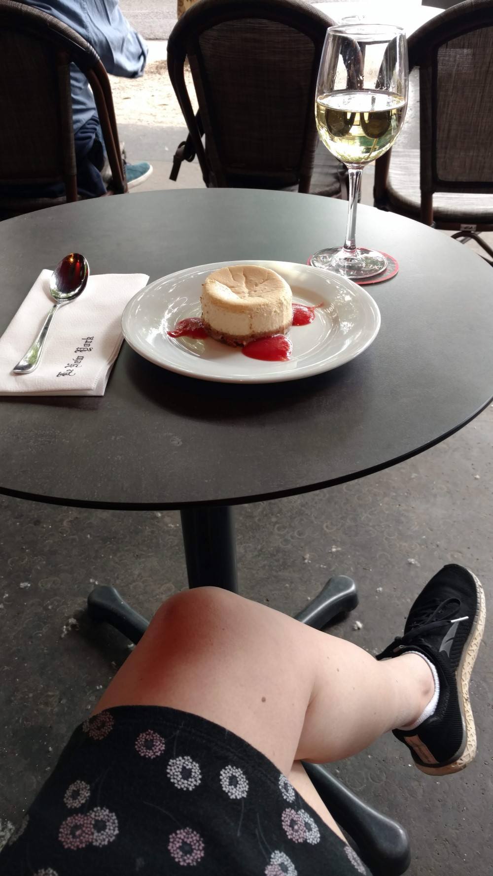 The New York cafe in Paris. On the table, cheesecake and wine. Under the table, comfortable shoes