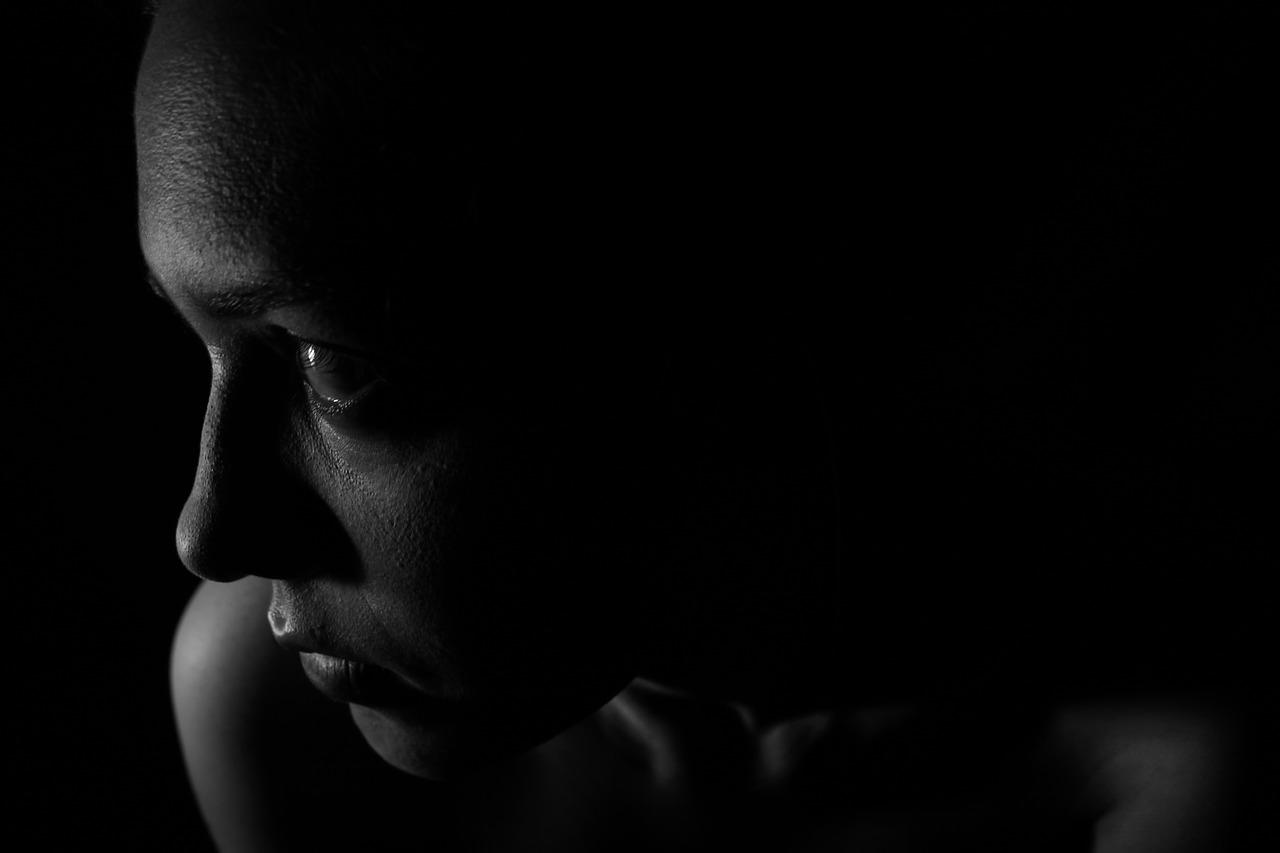girl in shadows looking darkly away