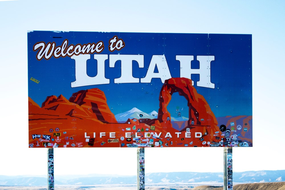 Billboard with mountains in the background that says Welcome to UTAH - LIFE ELEVATED