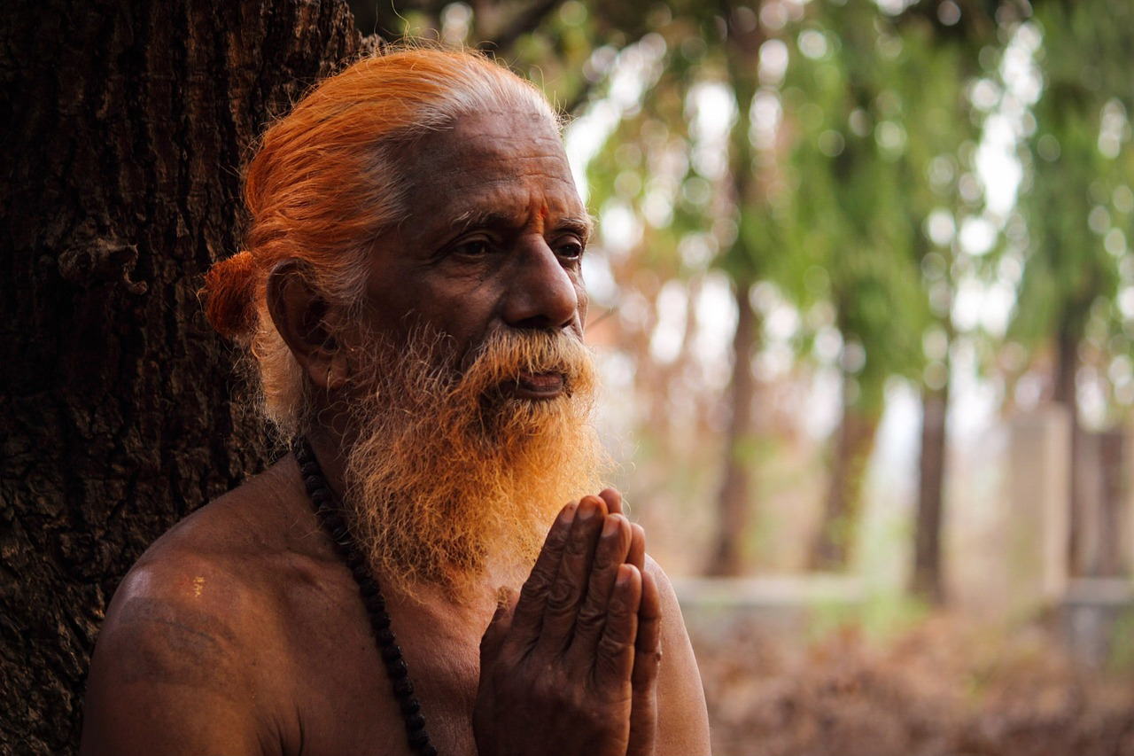 Elderly man with his hands together, praying or in meditation