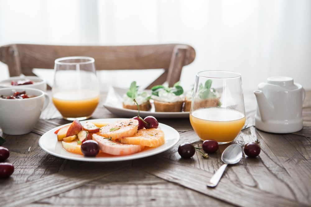 Table set with breakfast of fruit, tea, and cakes