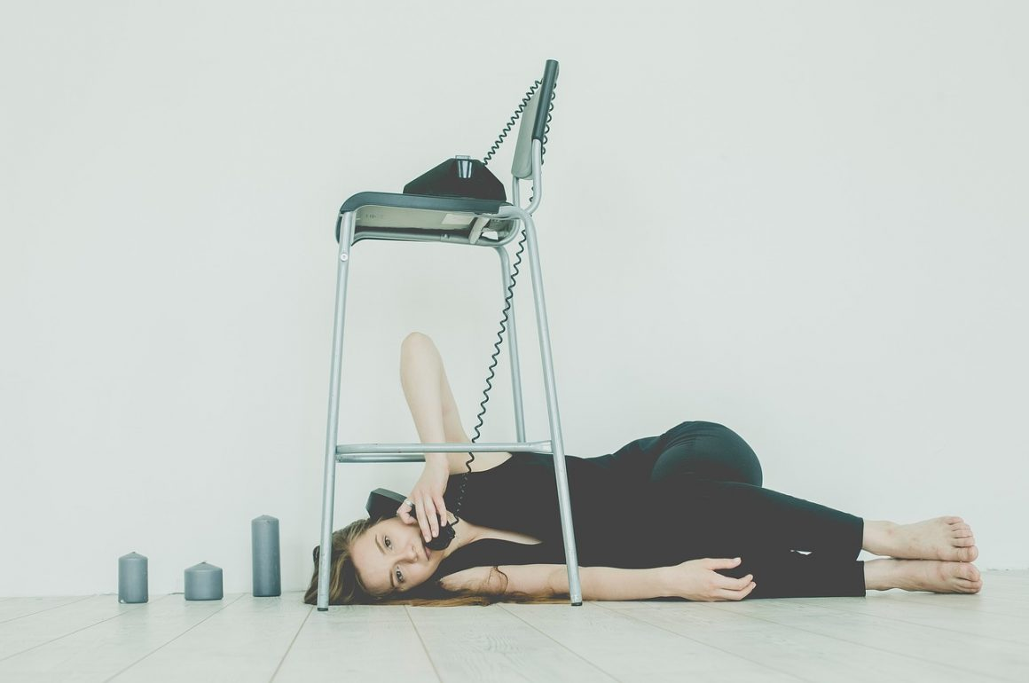 woman lying on the ground under a chair talking on an old-fashioned phone with a cord