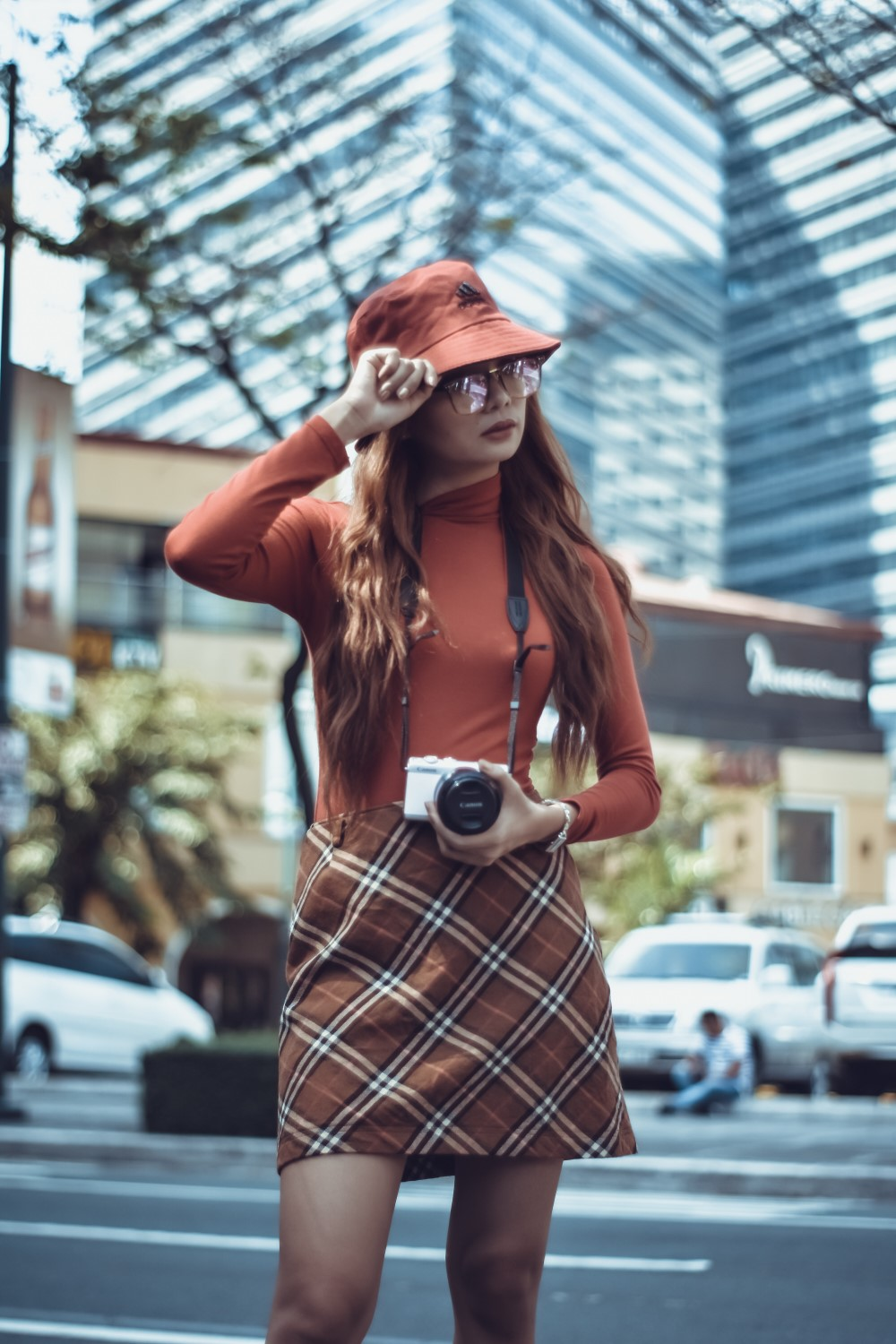 stylish woman in hat and plaid skirt with camera