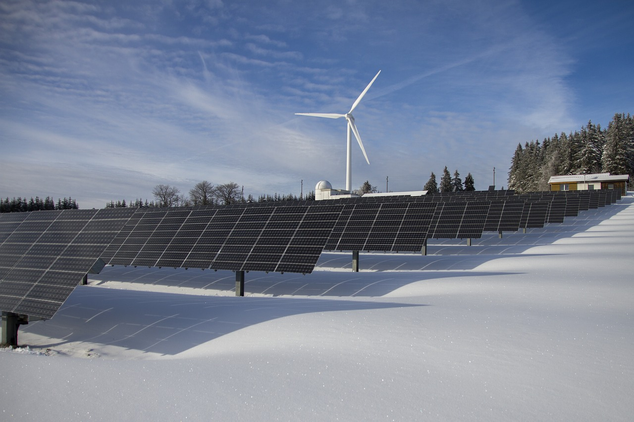 clean energy - renewable energy - wind turbine - solar panels - fighting climate change and global warming in the snow