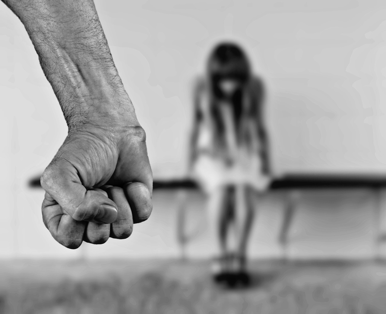 photo characterizing abuse - man's fist in foreground - woman bowing head in background