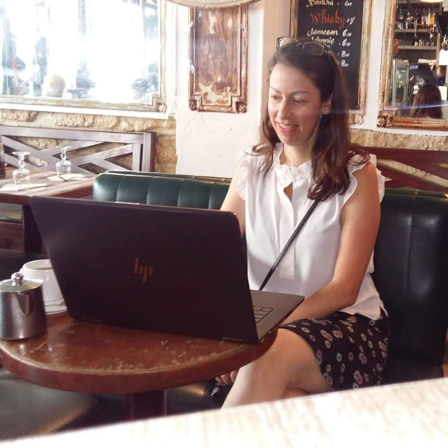 Liza Achilles working on a laptop in a Paris cafe