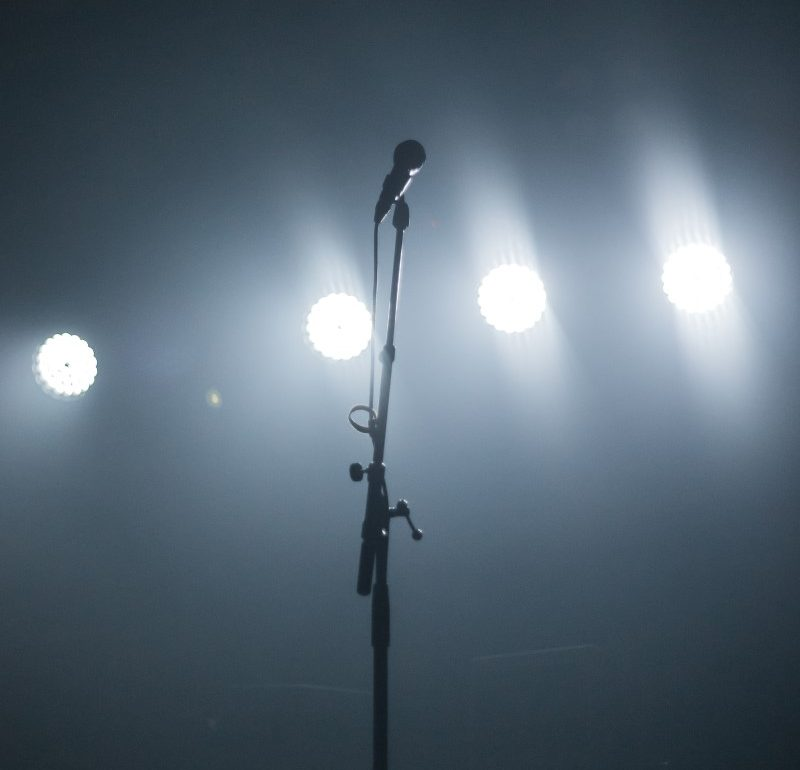tall solo microphone with stage lights at a performance