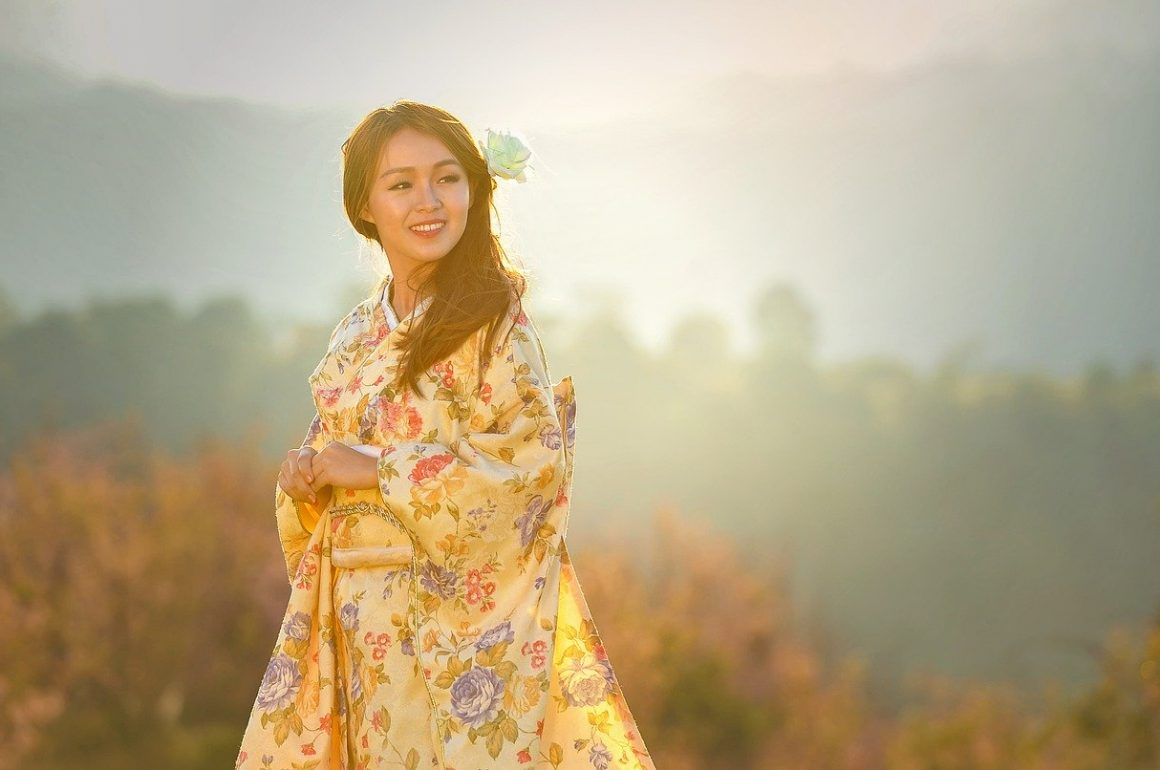 Asian woman in traditional dress with mountains in background