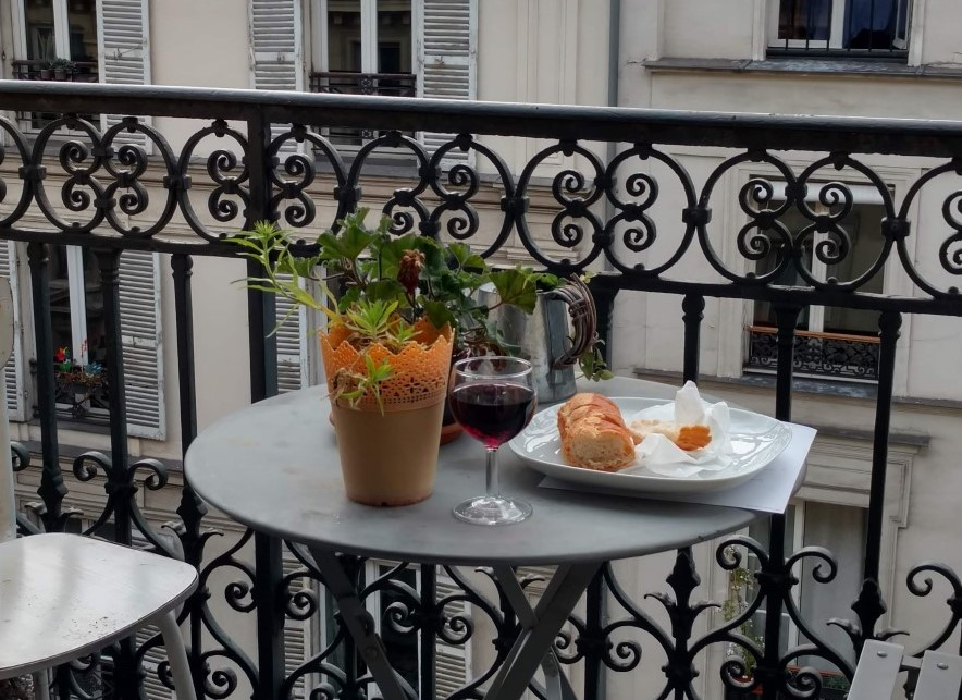 on a Paris balcony, a glass of red wine, a baguette, and a plant on a little table with two chairs