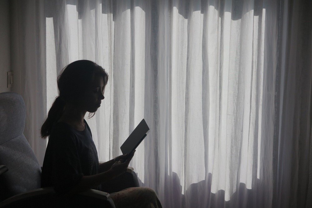 woman reading in darkened room