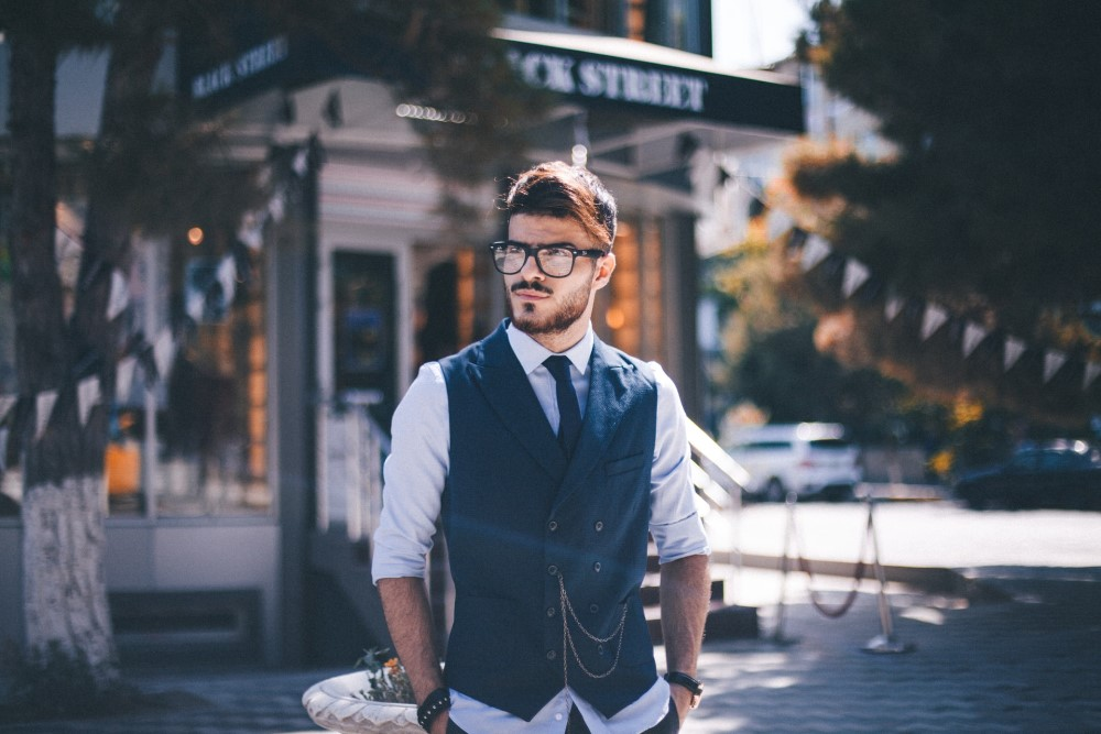 man about town wearing glasses, a tie and vest, a white shirt, and a chain, with hands in pockets, looking very cool and confident