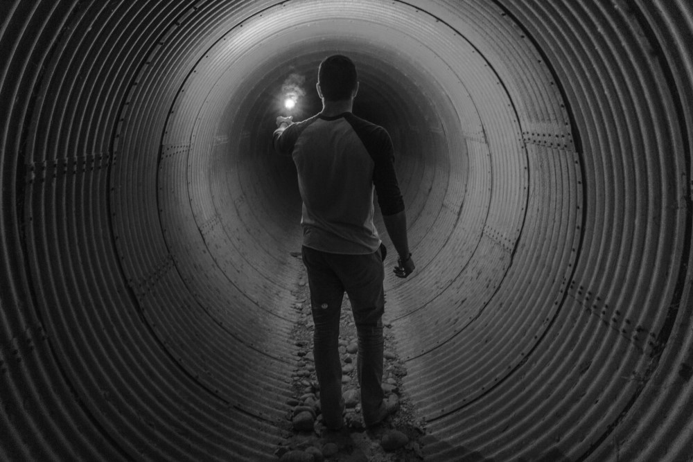 man in dark tunnel holding a light