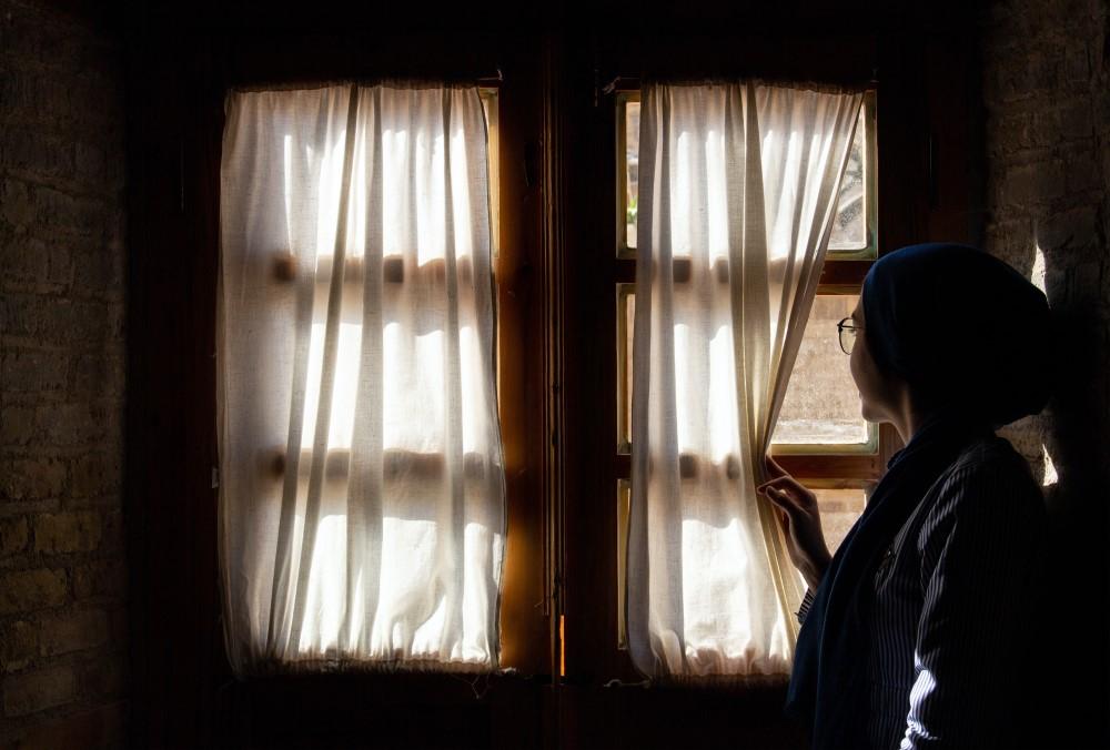 woman peeking outside past window curtain