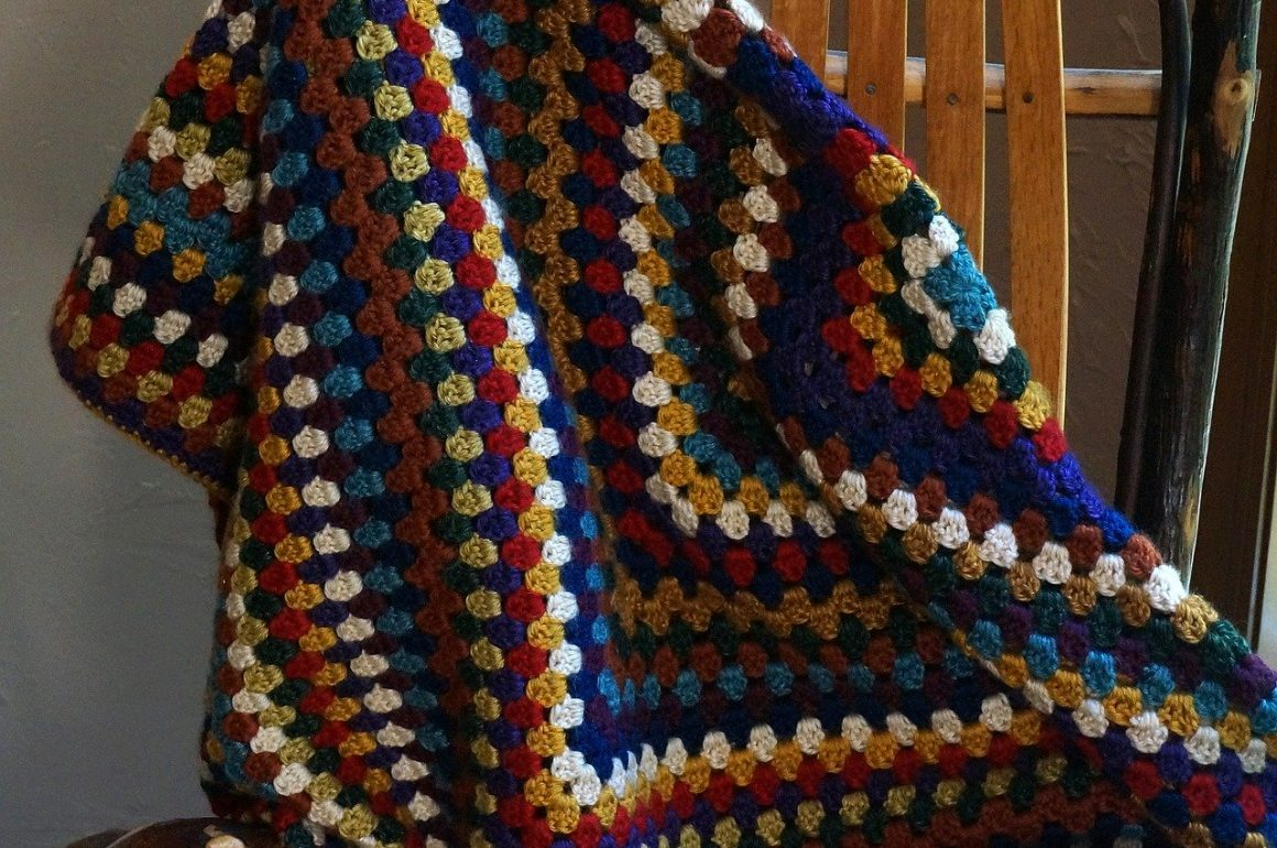 Granny square crocheted afghan draped from a chair