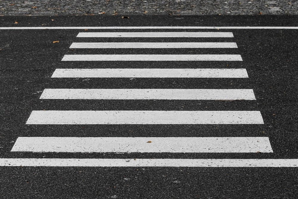crosswalk white stripes on dark pavement
