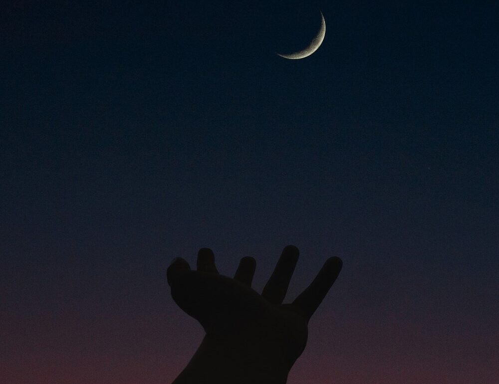 hand reaching up toward crescent moon