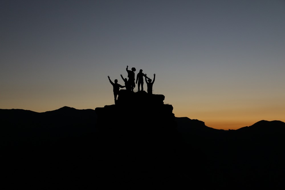 people in silhouette raising hands at dusk