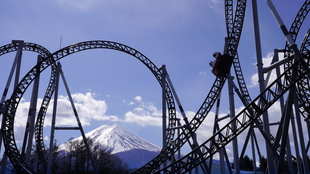 roller coaster with mountain and clouds and blue sky