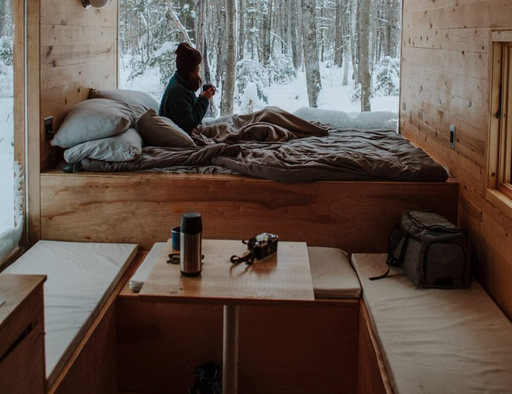 small room in winter as woman drinks hot beverage on a bed in a tiny house