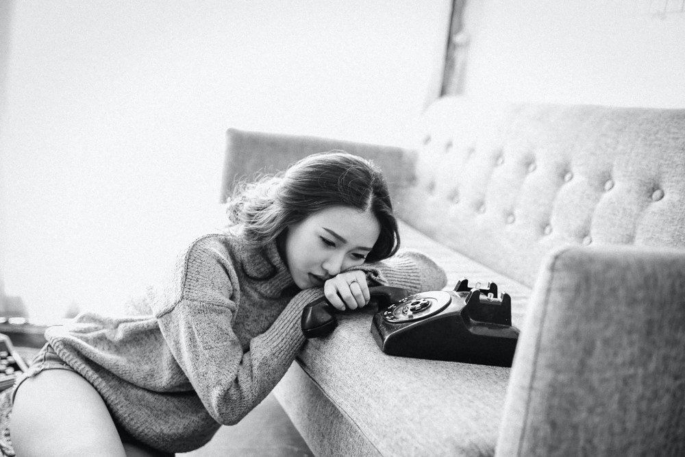girl holding old fashioned rotary phone by couch