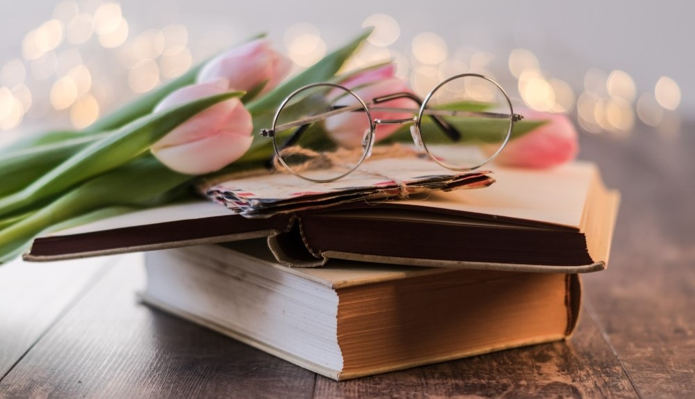 round glasses and pink flowers on top of old books and letters