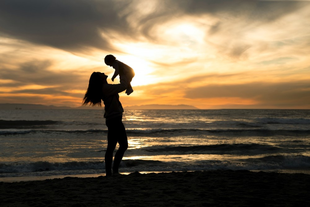 woman holding child before sea and sky