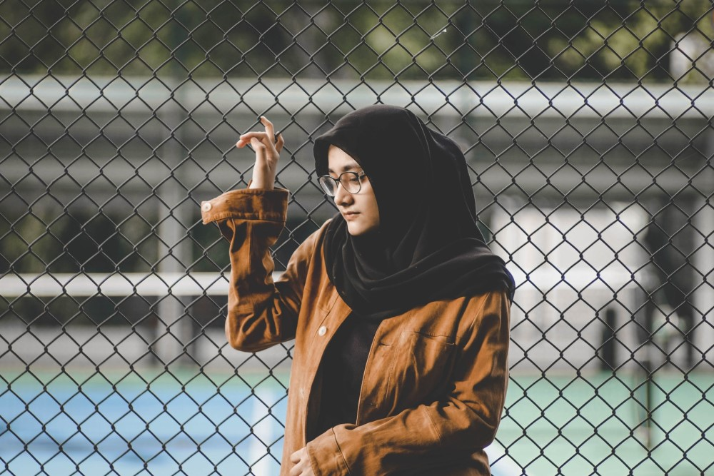 woman in black hijab scarf by chain link to tennis court