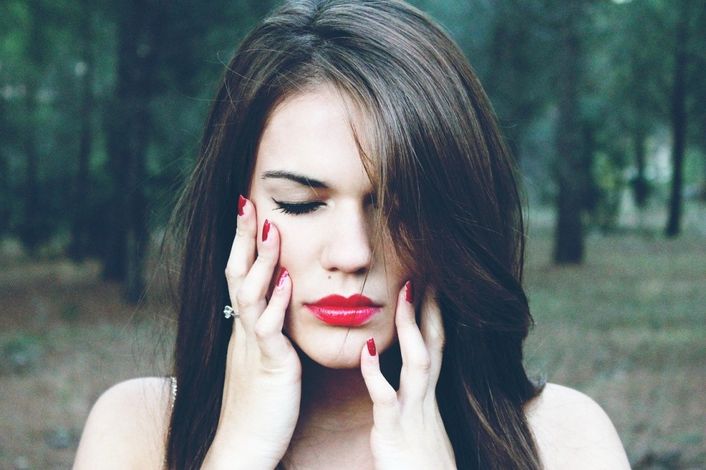 woman in forest with red lipstick and red nails holding her face in pain