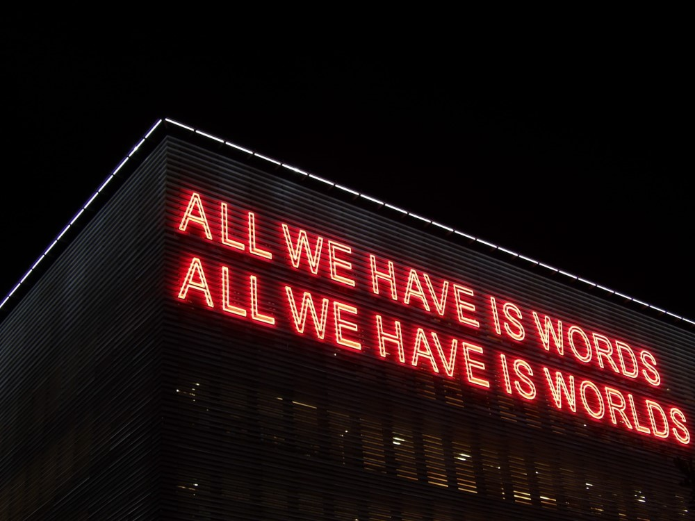 Neon sign that says ALL WE HAVE IS WORDS ALL WE HAVE IS WORLDS